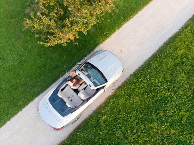 Flyg- sikt av den lyckade mannen som kör och tycker om hans lyxiga sportbil för silvercabriolet på sidan för öppet land royaltyfri fotografi