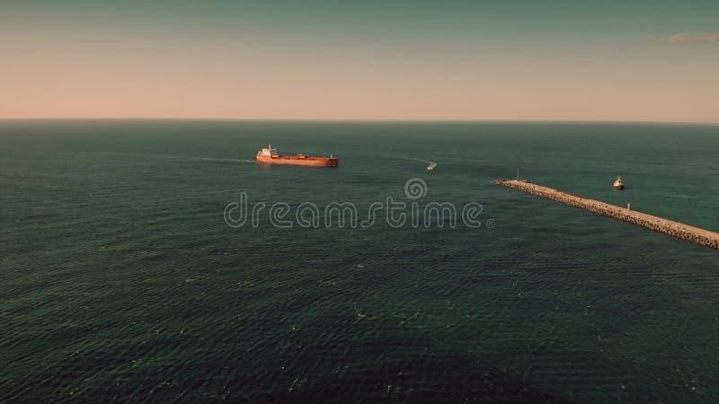 Flyg- sikt av den okända röda oljetanker som flyttar sig på havet nära hamnstad royaltyfri foto