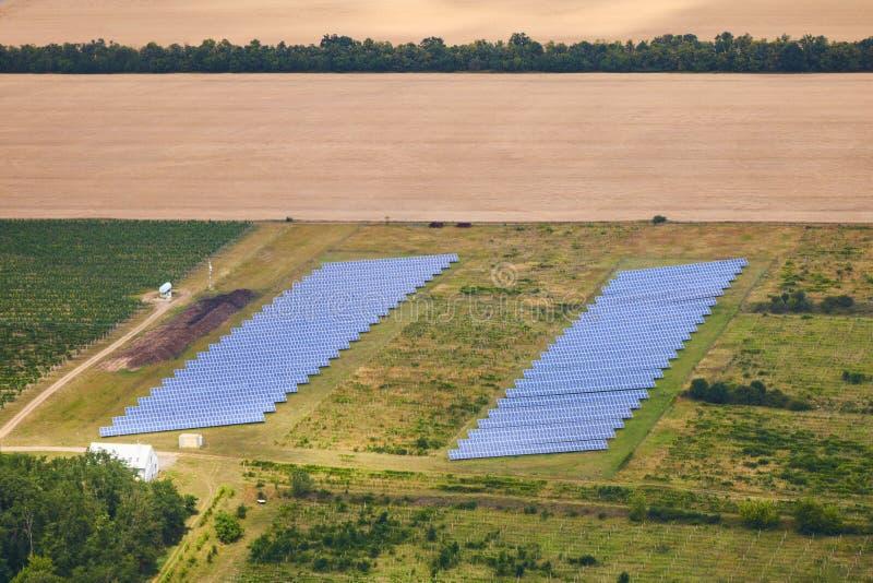 Flyg- sikt av den photovoltaic solpanelkraftverket på grönt fält arkivbilder