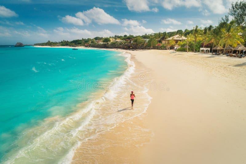 Flyg- sikt av den rinnande unga kvinnan p? den vita sandiga stranden arkivfoton