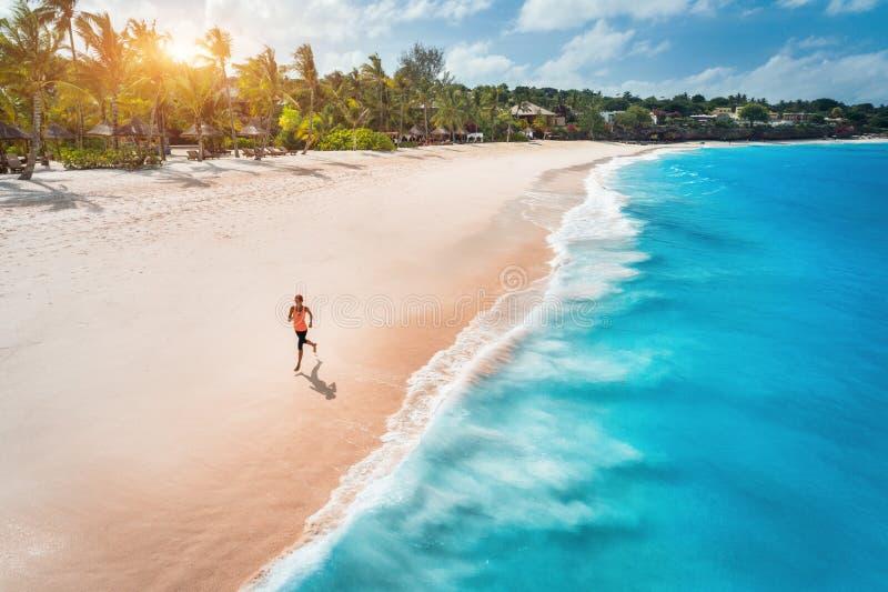 Flyg- sikt av den rinnande unga kvinnan p? den sandiga stranden arkivfoto