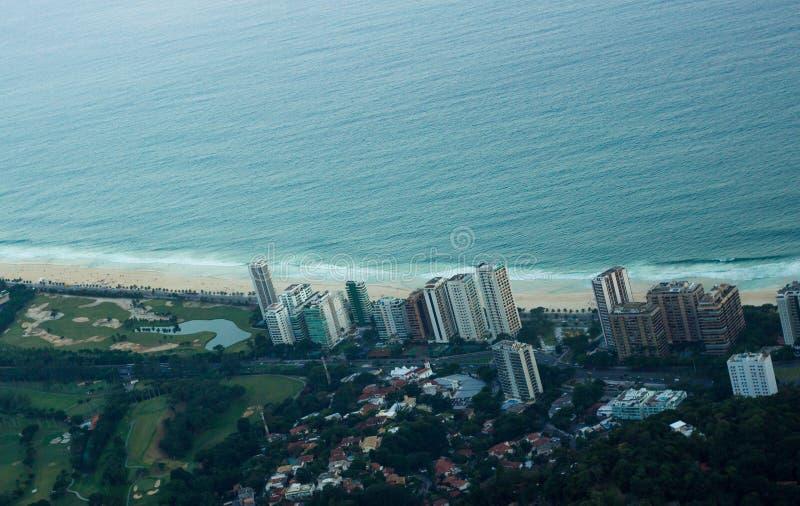 Flyg- sikt av den Rio de Janeiro stranden som fångar havet, sand, byggnad och skogen royaltyfri fotografi