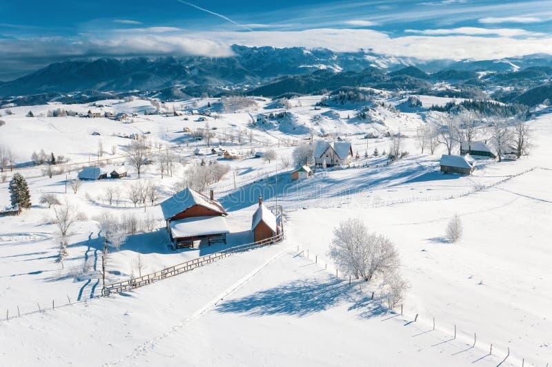 Flyg- sikt av den Sirnea byn som täckas med snö nära jul i Rumänien royaltyfri bild