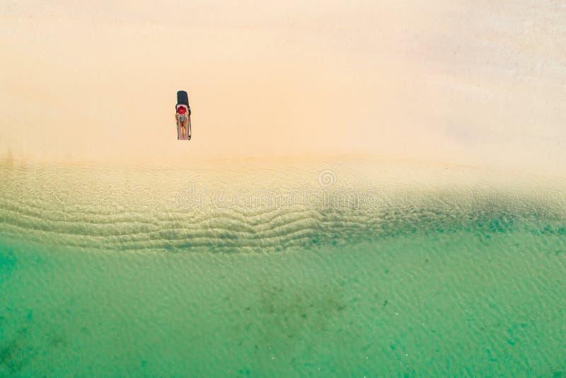 Flyg- sikt av den slanka kvinnan som solbadar att ligga p? en strandchairin Seychellerna Sommarseascape med flickan, h?rliga v?go royaltyfri bild