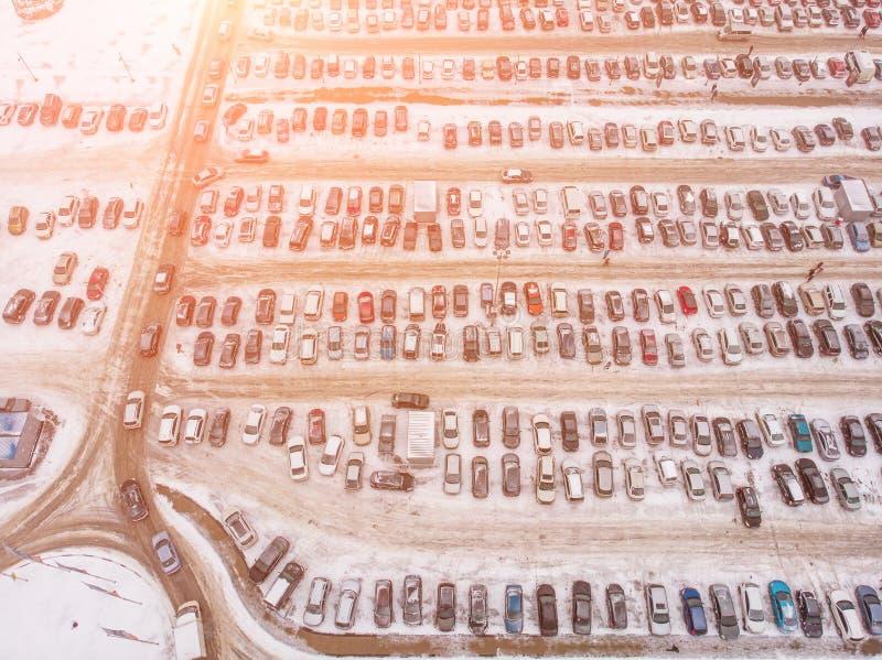 Flyg- sikt av den stora bilparkeringsplatsen med många bilar nära galleria eller köpcentrum i vinter med snö och solljuseffekt royaltyfri fotografi