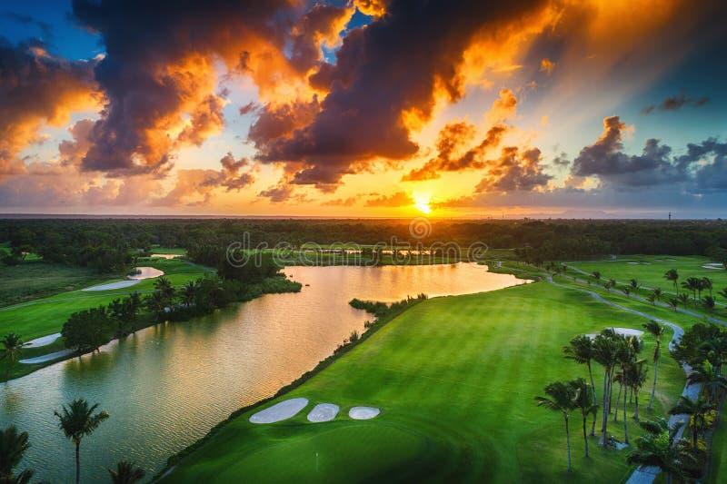 Flyg- sikt av den tropiska golfbanan på solnedgången, dominikan Republi royaltyfri foto