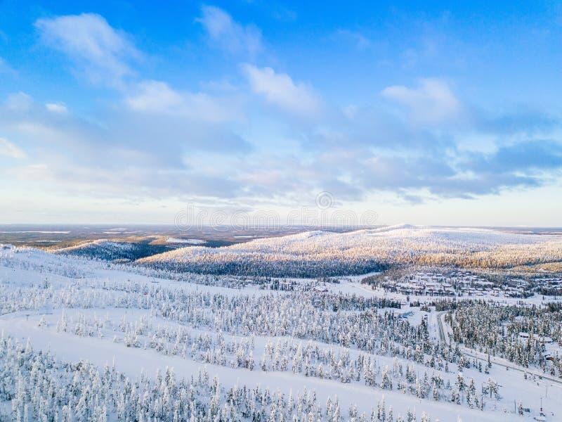 Flyg- sikt av den vinterskogen och vägen för snö den dolda Härligt lantligt landskap i Finland royaltyfria bilder