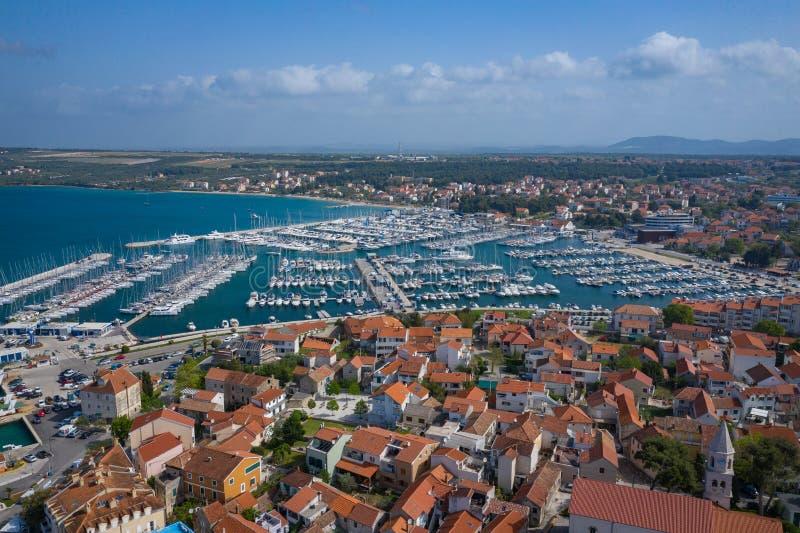 Flyg- sikt av den yachtklubban och marina i Biograd na Moru Sommartid i den Dalmatia regionen av Kroatien Kustlinje- och turkosva royaltyfri fotografi