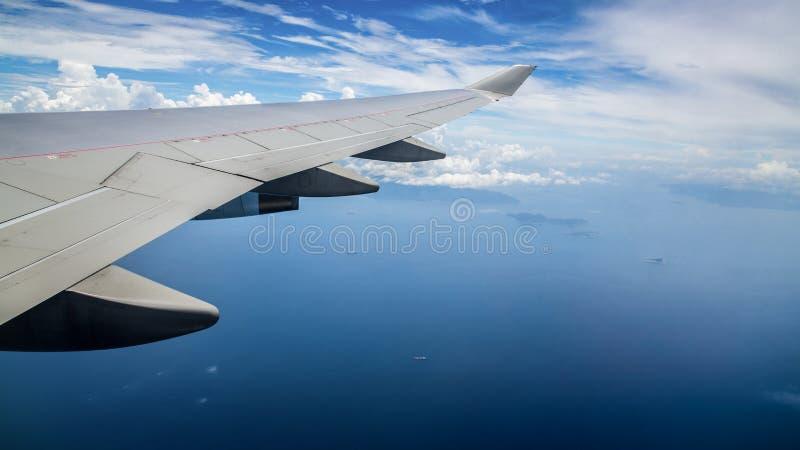 Flyg- sikt av det blåa havet från ett flygplanfönster Lopp f?rbi luft royaltyfri bild