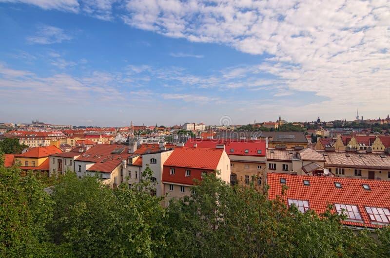 Flyg- sikt av det bostads- området i Prague Byggnader med tak för röd tegelplatta, många träd Färgrik vibrerande himmel royaltyfria foton