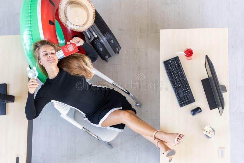 Flyg- sikt av det kvinnliga rymmande passet f?r avkopplad anst?lld som ?r klart att resa i arbetsplats av kontoret Begrepp f?r so royaltyfri bild