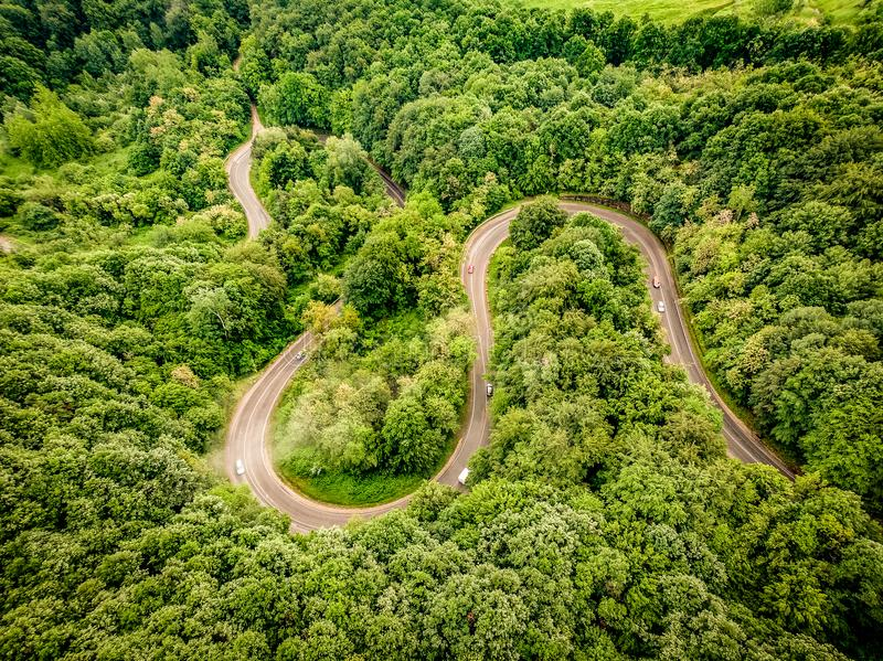 Flyg- sikt av en extrem slingrig väg upp i bergen fotografering för bildbyråer