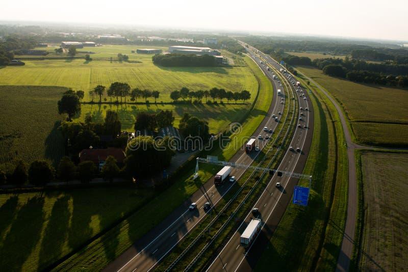 Flyg- sikt av en huvudväg med gröna fält arkivfoton