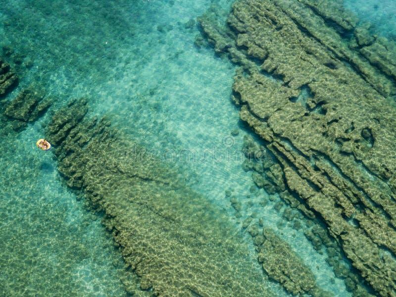 Flyg- sikt av en jolle i vattnet som svävar på ett genomskinligt hav Badare på havet Zambrone Calabria, Italien royaltyfri fotografi