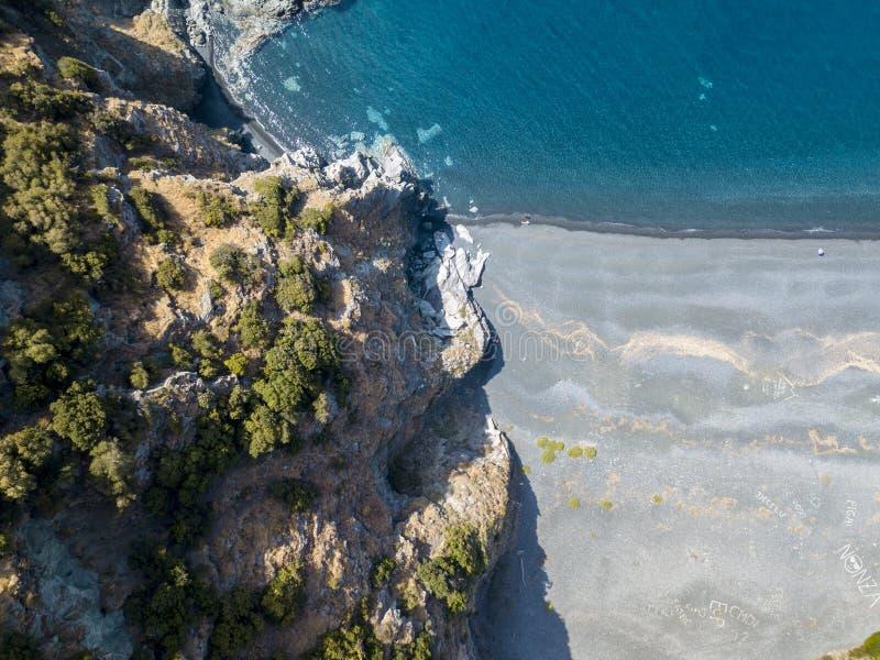 Flyg- sikt av en klippa som förbiser havet, svart strand, kommun av Nonza, halvö av Cap Corse, Korsika royaltyfri fotografi