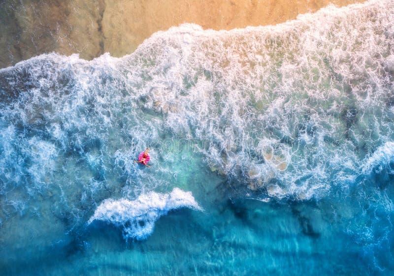 Flyg- sikt av en kvinnasimning med den rosa munkbadcirkeln royaltyfri bild