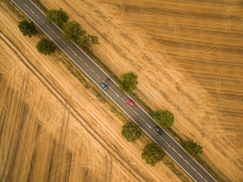 Flyg- sikt av en landsväg under fält royaltyfria bilder