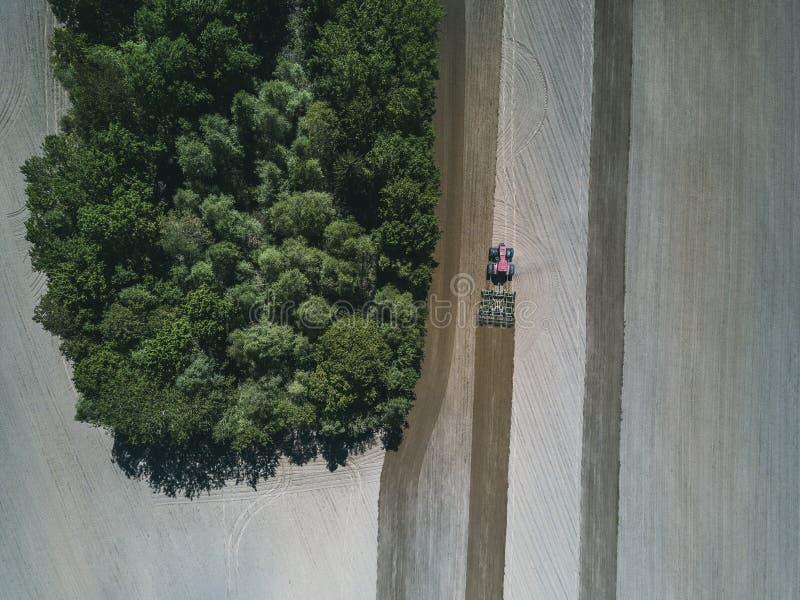 Flyg- sikt av en lantgårdtraktor i ett fält under att ploga av land för växande mat arkivfoton