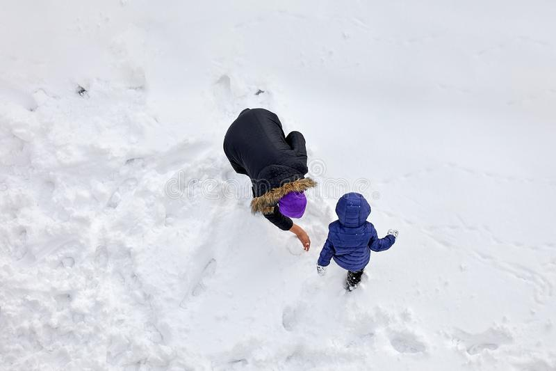 Flyg- sikt av en moder och hennes pyslek i den insnöade vintern royaltyfria foton