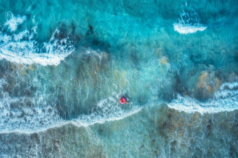 Flyg- sikt av en simma kvinna i det blåa havet med vågor royaltyfria bilder