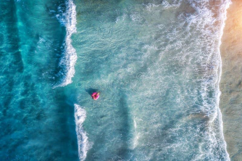 Flyg- sikt av en simma kvinna i det blåa havet med vågor arkivfoton