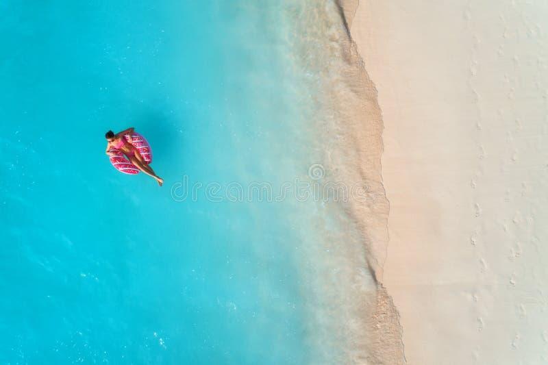 Flyg- sikt av en simma kvinna i havet p? solnedg?ngen arkivfoton