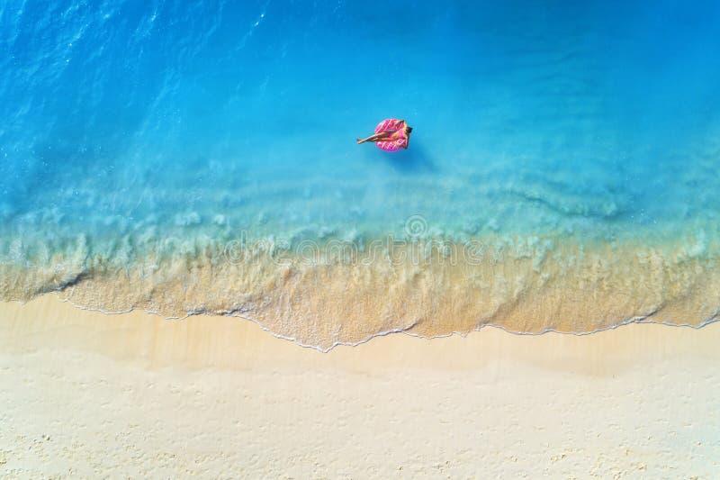 Flyg- sikt av en simma kvinna i havet p? solnedg?ngen royaltyfria foton