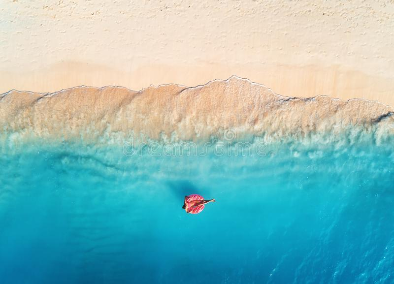 Flyg- sikt av en simma kvinna i havet p? solnedg?ngen arkivfoto