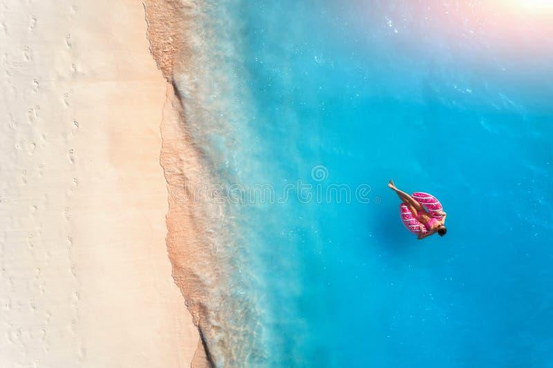 Flyg- sikt av en simma kvinna i havet p? solnedg?ngen arkivbilder