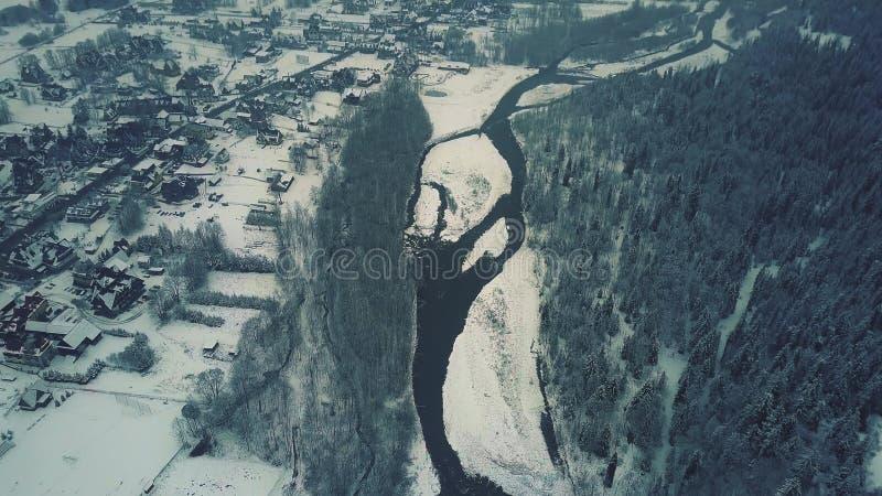 Flyg- sikt av en skog, en liten flod och ett typisk östligt - europeisk liten stad eller by i snön royaltyfri foto