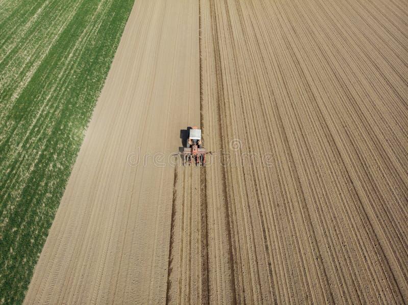 Flyg- sikt av en traktor som plogar fälten, flyg- sikt, ploga, sådd, skördjordbruk och som brukar, aktion royaltyfri bild