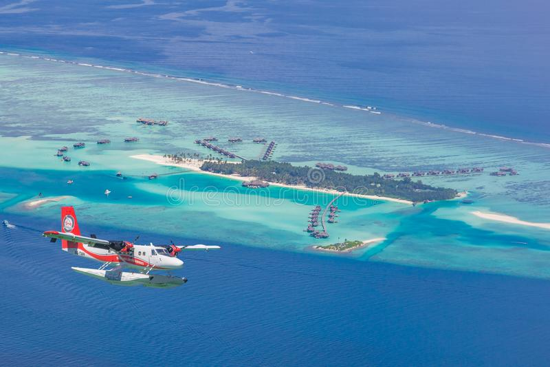 Flyg- sikt av en tropisk ö i det indiska havet med sjöflygplanet som att närma sig, Maldiverna arkivbild