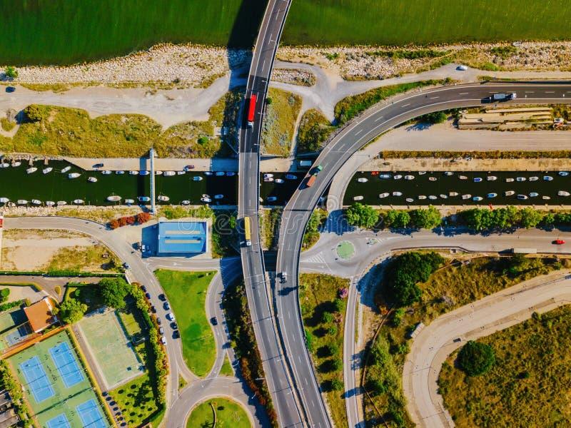 Flyg- sikt av en vägföreningspunkt och en flod med motoriska fartyg i Valencia royaltyfria bilder