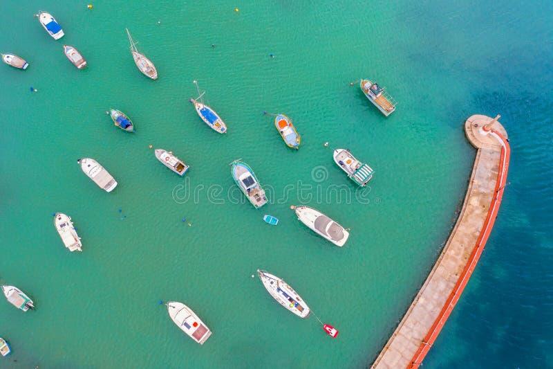 Flyg- sikt av fjärden med turkosvatten och många små fiskebåtar med bryggan och fyren royaltyfria bilder