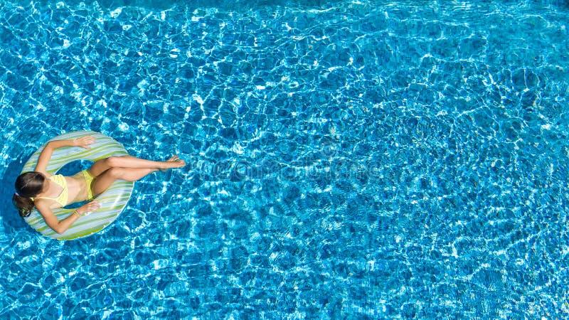 Flyg- sikt av flickan i simbassäng från över, ungebad på den uppblåsbara cirkelmunken i vatten på familjsemester arkivfoto