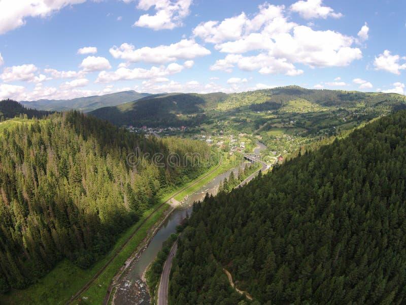Flyg- sikt av floden nära bergvägen med bron royaltyfria foton