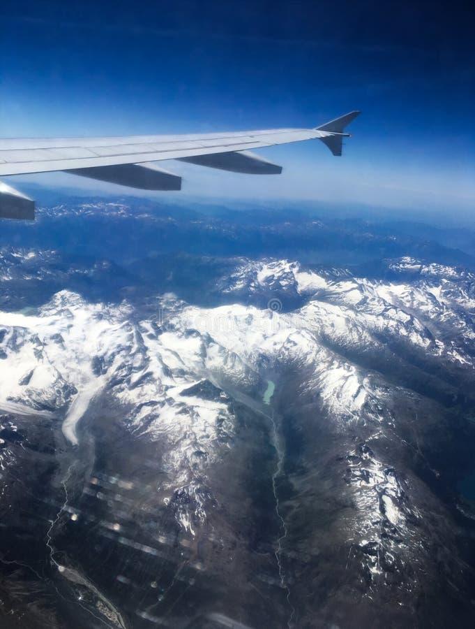 Flyg- sikt av flygplanvingen och de schweiziska fjällängarna Is täckte kanter arkivfoto