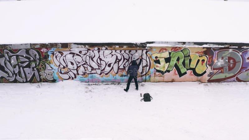 Flyg- sikt av gatakonstnären i mörk kläder som besprutar en grafitti på en vägg i vinter actinium f?r grafittigata f?r konst f?rg arkivbild