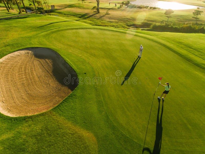 Flyg- sikt av golfare på sättande gräsplan royaltyfri foto