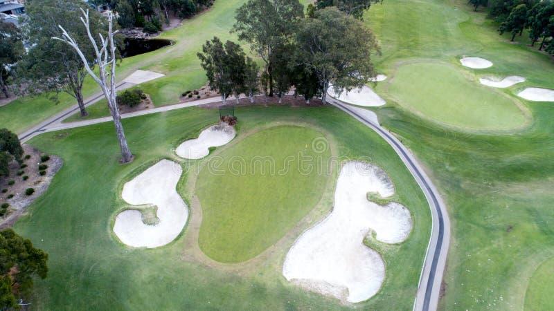 Flyg- sikt av golfbanagräsplan med flaggan, bunker, fördämningar, farleder Sydney Australia arkivbilder