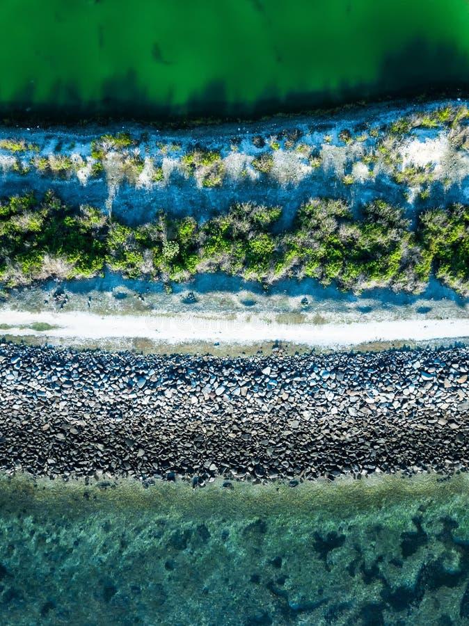 Flyg- sikt av grusvägen i - mellan av sjön och havet på den serangan stranden bali, arkivbilder