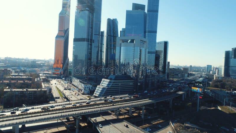 Flyg- sikt av huvudvägen med rörande bilar och höga moderna skyskrapor på bakgrunden i solig sommardag mot blått royaltyfri foto