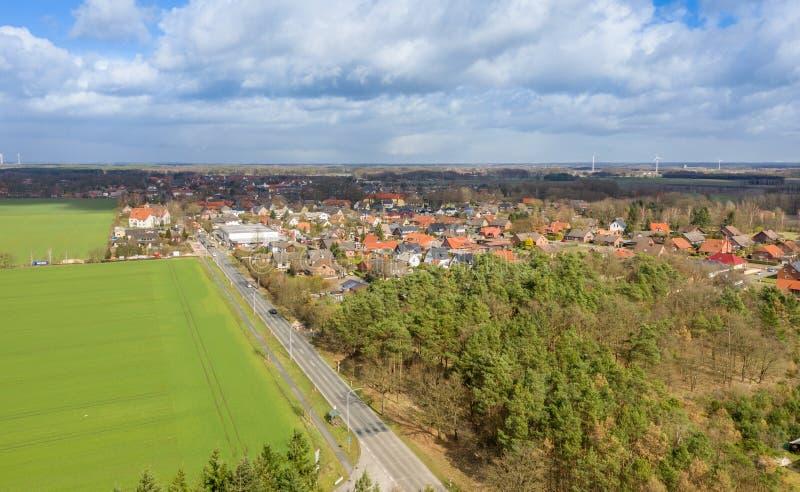 Flyg- sikt av ingången av en tysk liten stad med en landsväg mellan fält och trän för utvecklingen av byn arkivbild