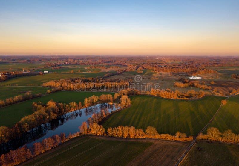 Flyg- sikt av jordbruks- fält, träd och en sjö - aftonsol, guld- timme royaltyfria bilder