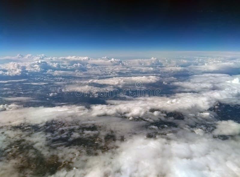Flyg- sikt av jorden från hög höjd med mörker - blå himmel och olika typer av vita moln med snö på ett bergigt landskap royaltyfri fotografi