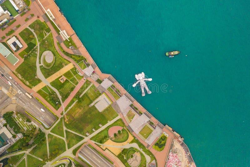 Flyg- sikt av KAWS-följet, jätte- skulptur som svävar på vatten Diagram i Victoria Harbour, Hong Kong Republiken Kina arkivfoto
