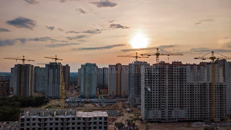 Flyg- sikt av konstruktionsplatsen av bostadsområdebyggnader med kranar på solnedgången från över, stads- horisont royaltyfria bilder