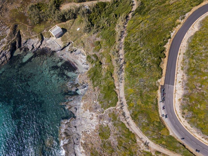 Flyg- sikt av kusten av Korsika, slingriga vägar och små viker Motorcyklister som parkeras på kanten av en väg france royaltyfri foto