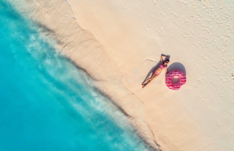 Flyg- sikt av kvinnan med badcirkeln p? den sandiga stranden royaltyfri foto
