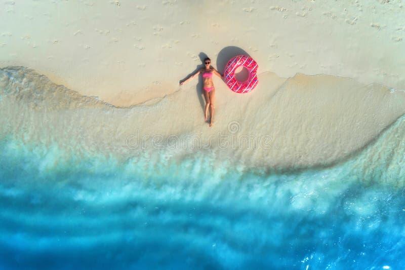 Flyg- sikt av kvinnan med badcirkeln p? den sandiga stranden arkivbilder